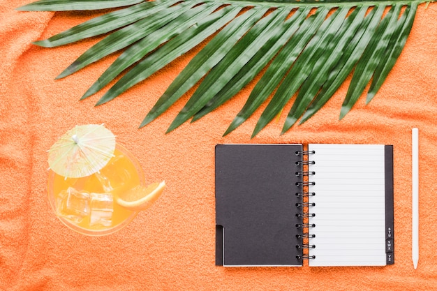 Composition de stylo cahier cocktail et de feuilles Photo gratuit