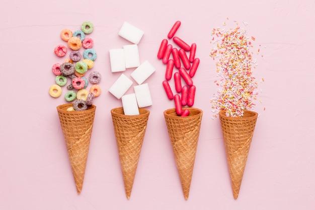 Composition de vinaigrettes au sucre, pilules rouges et cornets de glace Photo gratuit
