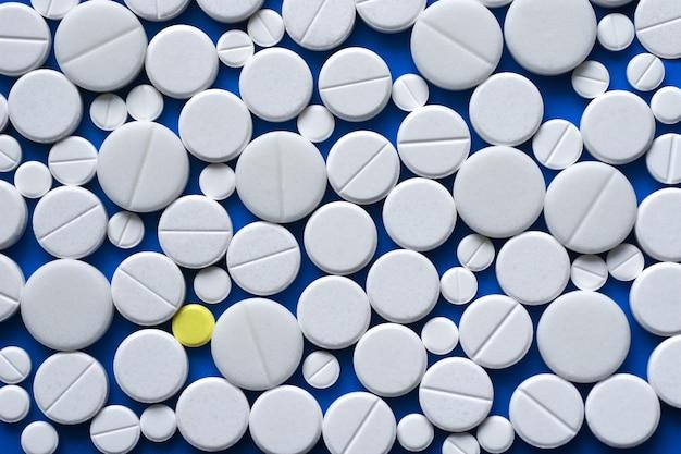 Comprimés jaunes et blancs dispersés sur une table médicale bleue Photo Premium