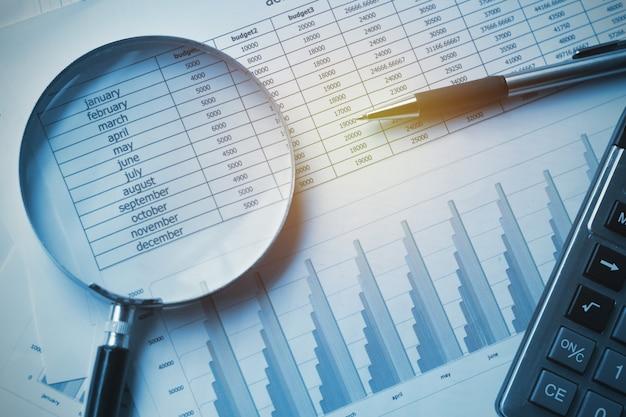 Comptabilité des documents commerciaux avec une calculatrice, un stylo et une loupe. Photo Premium