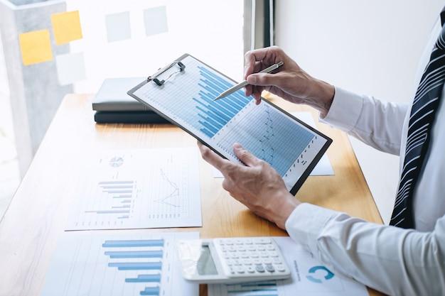 Comptable d'affaires travaillant à l'analyse et au calcul des dépenses, rapport financier annuel, état du bilan et analyse du graphique et du diagramme du document, effectuant la prise de notes en rapport Photo Premium