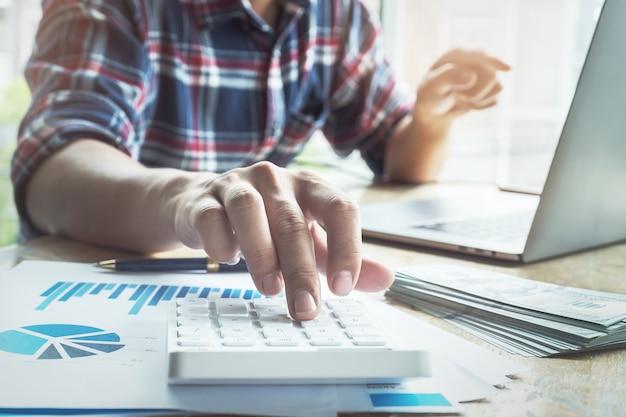 Le comptable appuie sur la calculatrice pour calculer vérifier l'exactitude du budget d'investissement Photo Premium