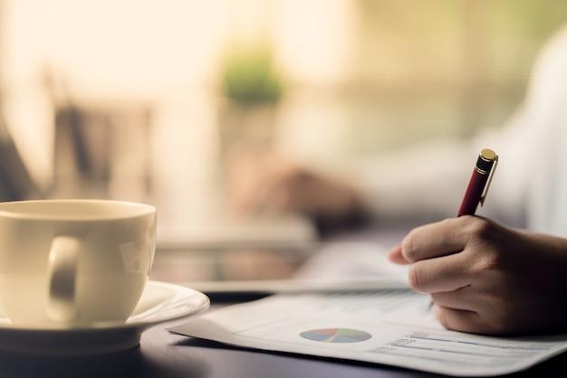 Le comptable vérifiant les documents sur le graphique et le graphique financier et fiscal Photo Premium