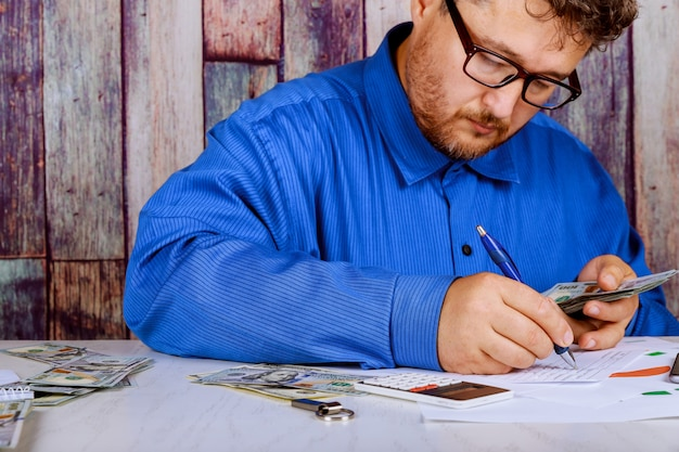 Compte l'argent et écrit le résultat sur la note. billets d'un dollar sur la table comptant des billets en dollars. Photo Premium