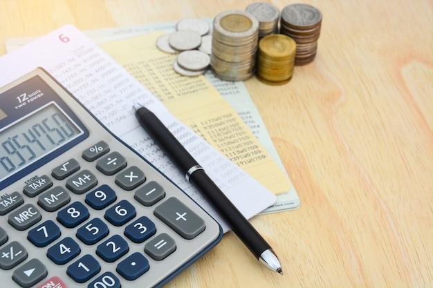 Compte épargne, Calculatrice, Stylo Et Tas De Pièces Sur Fond De Table En Bois Photo Premium