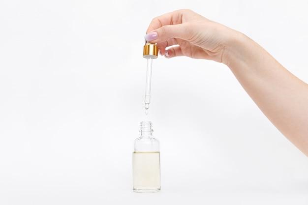 Compte-gouttes bouteille en verre maquette. goutte grasse tombe de pipette cosmétique sur fond blanc Photo Premium