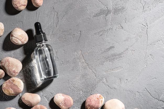 Compte-gouttes D'huile D'essence De Soins De La Peau Dans Une Bouteille En Verre Près De Cailloux Photo Premium