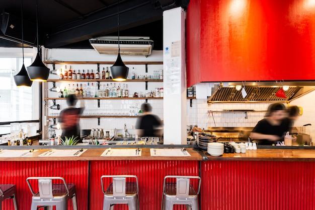 Comptoir de cuisine industriel rouge décoré dans un style loft comprenant du bois, un mur blanc et une tôle de zinc ondulée rouge. Photo Premium