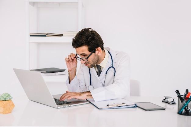 Concentration d'un jeune médecin travaillant sur un ordinateur portable dans une clinique Photo gratuit