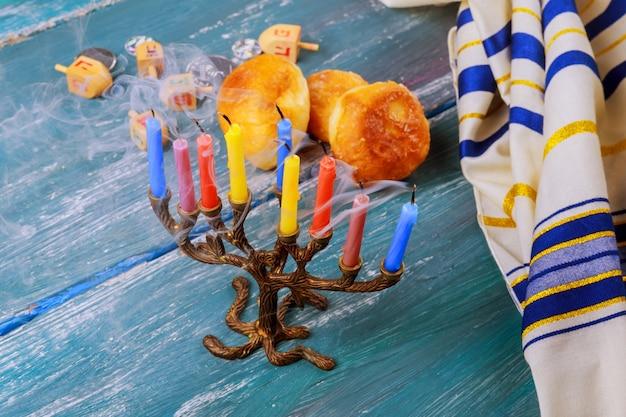 Concentration sélective de la fête juive de hanoukka avec menorah traditionnelle, beignets Photo Premium