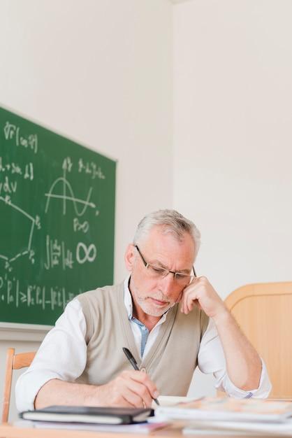 Concentré ancien professeur écrit dans un cahier Photo gratuit