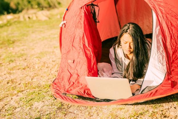 Concentré, femme, utilisation, ordinateur portable, mensonge, dans, tente Photo gratuit
