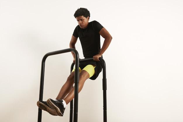 Concentré Jeune Athlète Afro-américain En Vêtements De Sport Noir Effectuant Des Rangées De Poids Corporel Sur Des Barres Mobiles Isolés Sur Blanc Photo gratuit