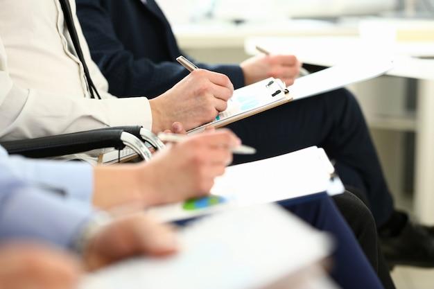 Concentrez-vous Sur Les Mains Des Travailleurs Intelligents écrivant Quelque Chose Dans Un Dossier Papier Avec Une Grande Concentration. Les Gestionnaires Discutent D'un Important Contrat D'entreprise. Concept De Réunion D'entreprise Photo Premium