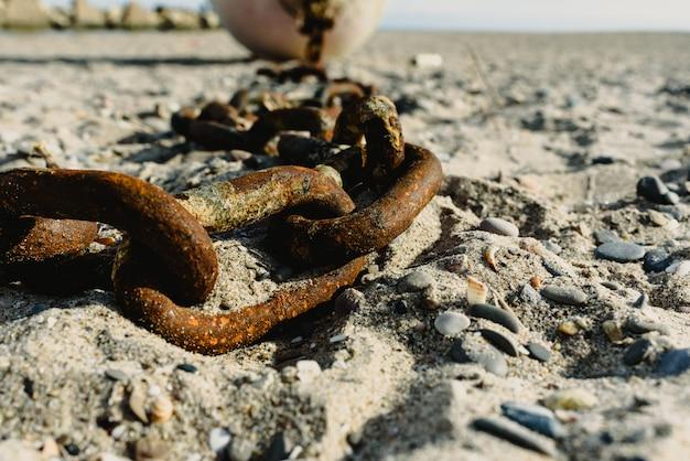 Concept d'abandon, vieilles chaînes rouillées et cassées jetées dans le sable d'une plage sale. Photo Premium