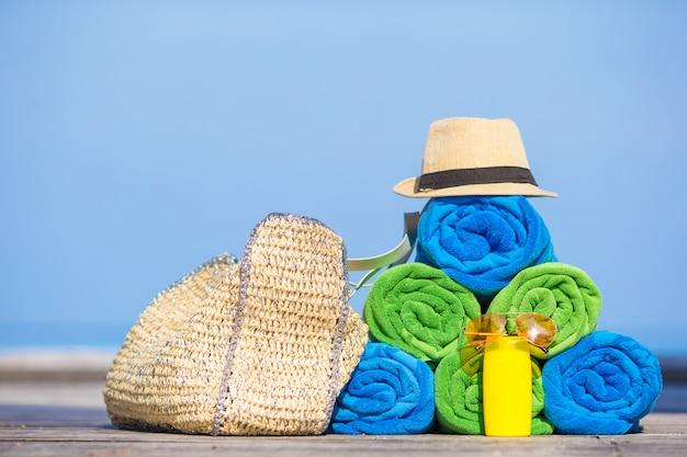 Concept d'accessoires de vacances d'été et de plage - gros plan de serviettes colorées, chapeau, sac et protection solaire Photo Premium