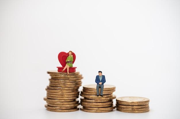 Concept D'affaires, D'argent, De Famille Et De Planification. Businesswoman Figure Miniature Gens Assis Sur Coeur Rouge Avec Homme D'affaires Sur Le Dessus De La Pile De Pièces D'or Photo Premium