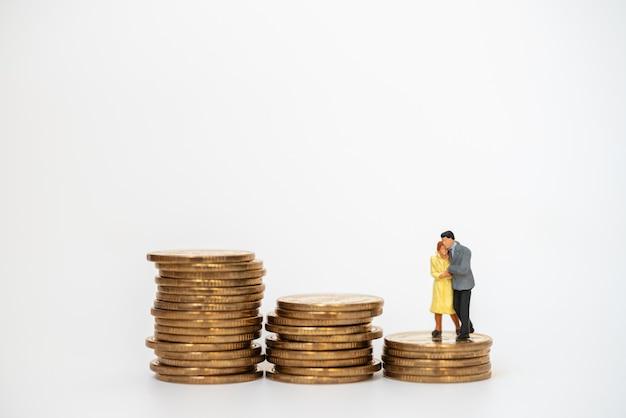 Concept D'affaires, D'argent, De Famille Et De Planification. Homme D'affaires Et Femme Figure Miniature Gens Câlin Et Marchant Sur Une Pile Instable De Pièces D'or Photo Premium