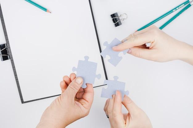 Concept d'affaires avec les mains tenant des morceaux de puzzle Photo gratuit