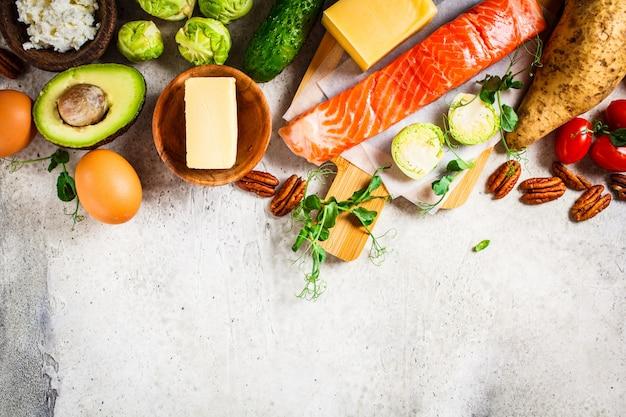 Concept alimentaire équilibré de régime. poisson, œufs, fromage, noix, beurre et légumes Photo Premium