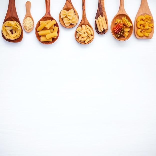 Concept d'aliments italiens et design de menus. différentes sortes de pâtes sur fond en bois blanc Photo Premium