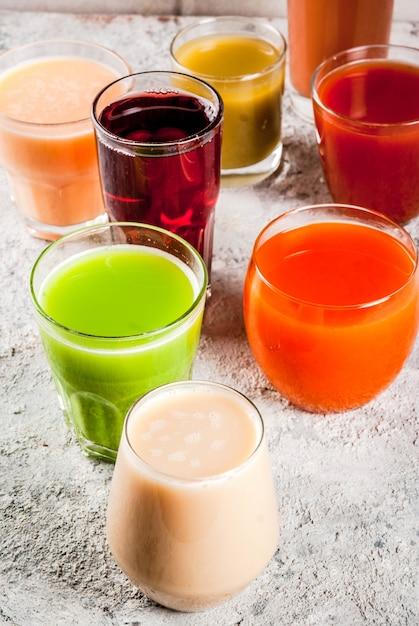 Concept d'aliments sains différents jus de fruits et légumes smoothie dans des verres Photo Premium