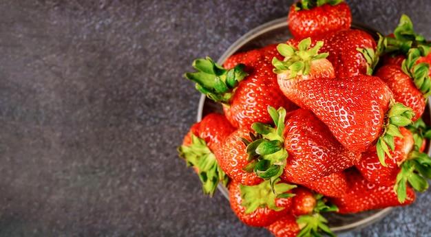 Concept D'aliments Sains Fraises En Plaque Sur Une Surface Sombre. Photo Premium