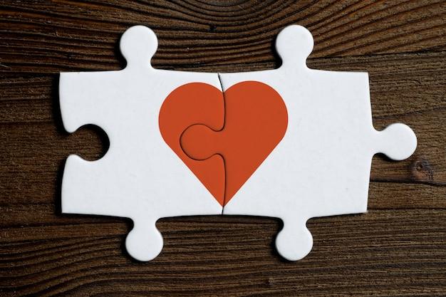 Le Concept De L'amour Mutuel. Morceaux D'un Puzzle Blanc Connecté Avec Coeur Rouge Sur Un Fond En Bois. Photo Premium