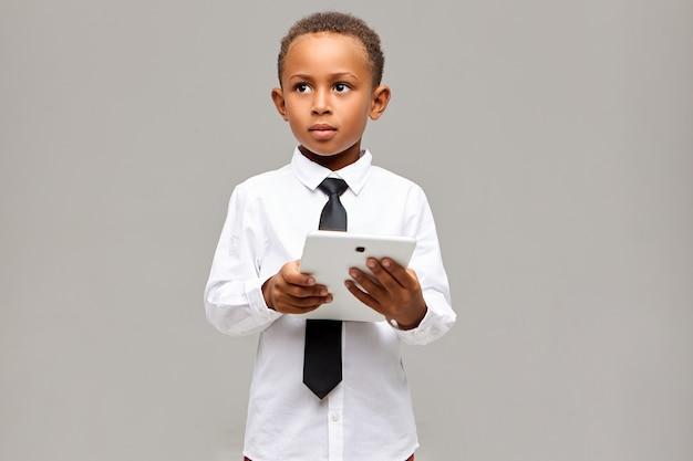 Concept D'apprentissage, D'éducation, De Technologie Et De Communication. Bel étudiant Africain Intelligent En Uniforme Scolaire Posant Avec Tablette Tactile Numérique, Utilisant Une Connexion Internet Sans Fil Photo gratuit