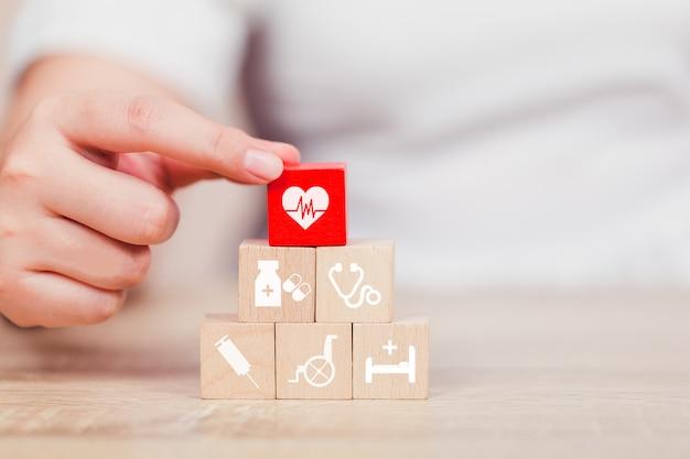 Concept d'assurance maladie, main organisant l'empilement de blocs de bois avec l'icône de soins de santé médical. Photo Premium