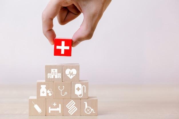 Concept d'assurance maladie, main organisant l'empilement de blocs de bois avec l'icône des soins de santé médicaux, pour la santé Photo Premium