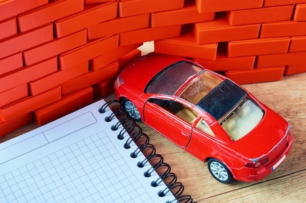 Concept d'assurance voiture. une voiture rouge s'est écrasée dans un mur de briques Photo Premium