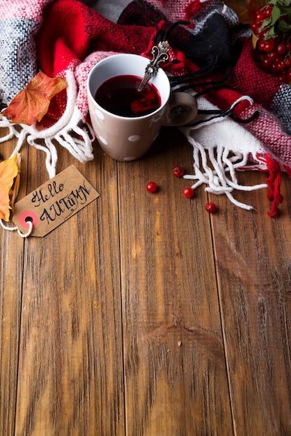 Concept d'automne automne avec couverture tricotée et thé chaud aux baies, feuille d'automne Photo Premium
