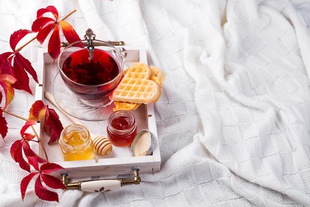 Concept d'automne automne avec couverture tricotée et thé chaud avec gaufres, confiture, miel Photo Premium