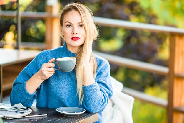 Concept de l'automne - belle femme buvant du café dans un parc en automne sous le feuillage d'automne Photo Premium