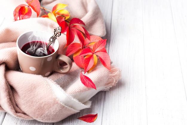 Concept de l'automne. une tasse de thé en bonne santé dans les feuilles rouges jaunes avec une écharpe beige Photo Premium