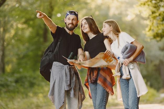 Concept D'aventure, De Voyage, De Tourisme, De Randonnée Et De Personnes. Groupe D'amis Souriants Dans Une Forêt. Photo gratuit