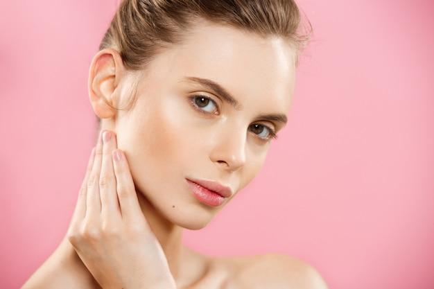 Concept de beauté - belle femme caucasienne avec une peau propre, un maquillage naturel isolé sur un fond rose brillant avec un espace de copie. Photo gratuit