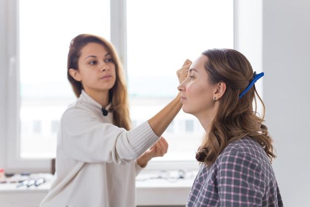 Concept De Beauté Et Cosmétiques - Maquilleur Faisant Professionnel De La Jeune Femme Photo Premium