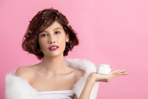 Concept de beauté. femme tient une crème hydratante dans sa main Photo gratuit
