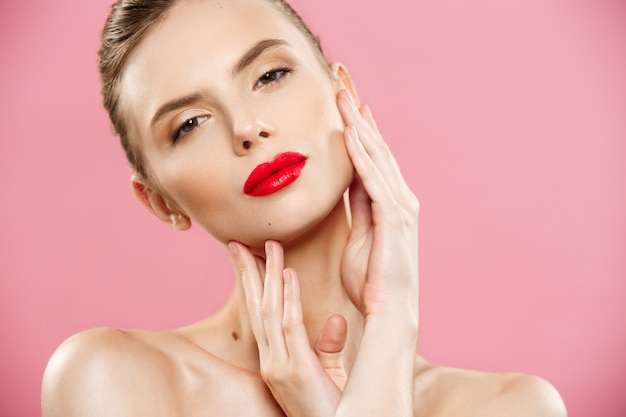 Concept de beauté - gros plan portrait de jeune femme brune jeune femme. beauty model girl aux sourcils brillants, maquillage parfait, lèvres rouges, toucher son visage. isolé sur fond rose Photo gratuit