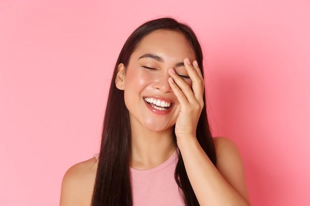 Concept De Beauté, Mode Et Style De Vie. Gros Plan De La Belle Jeune Fille Asiatique Sans Acné Ni Imperfections, Sourire Blanc, Toucher Le Visage Et Air Heureux, Debout Sur Le Mur Rose. Photo Premium