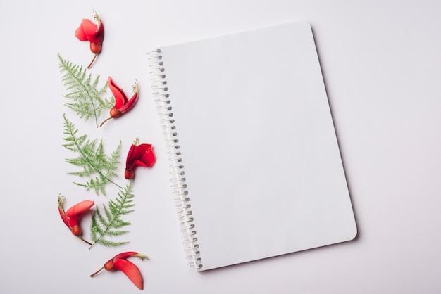 Concept de belles fleurs avec cahier Photo gratuit
