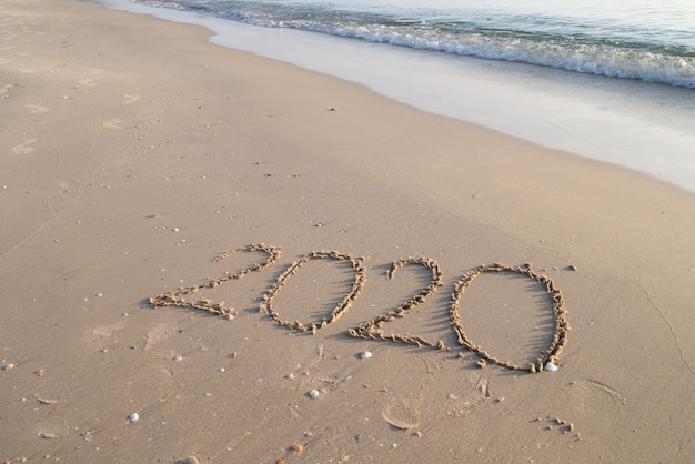 Concept de bonne année 2020 avec lettre de sable sur l'espace de copie de plage Photo Premium