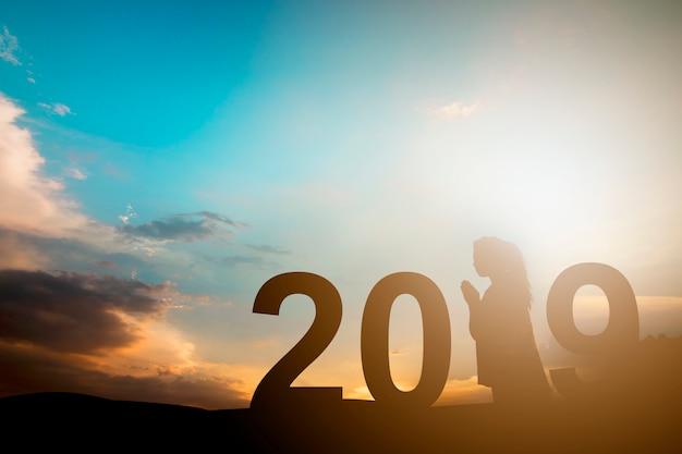 Concept de bonne année, silhouette de femme en prière en 2019 Photo Premium