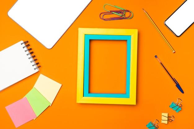 Concept de bureau vue de dessus avec fond orange Photo gratuit
