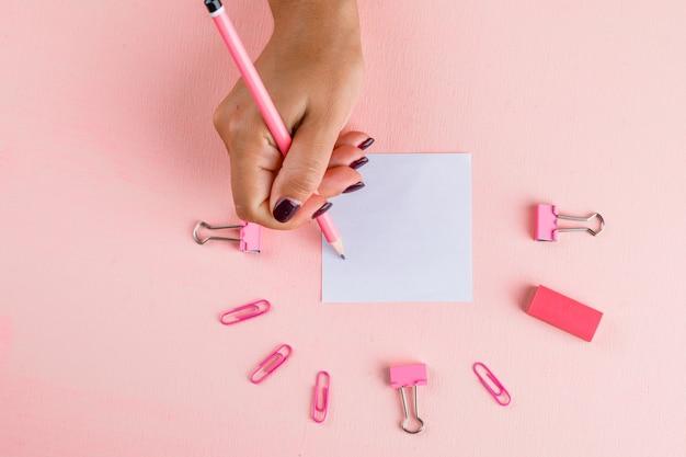 Concept De Célébration Avec Du Papier Et Des Agrafes De Reliure, Gomme Sur Table Rose à Plat. Femme écrivant Sur Pense-bête. Photo gratuit
