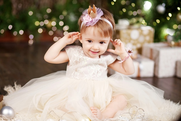 Concept de célébration de noël et du nouvel an. jolie petite fille en robe blanche jouant et étant heureuse de l'arbre de noël et des lumières. vacances d'hiver. Photo Premium