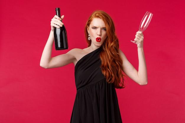 Concept De Célébration, De Vacances Et De Femmes. Impertinente Et Insouciante, Excitée Jeune Femme Rousse S'amusant à La Fête, Soulevant Une Bouteille De Champagne Et Un Verre, Invitant Tout Le Monde à Boire, à L'audace Photo Premium