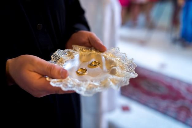 Concept De Cérémonie De Mariage à L'église. Anneaux D'or Sur L'assiette. Arrière-plan Flou. Fermer. Photo Premium